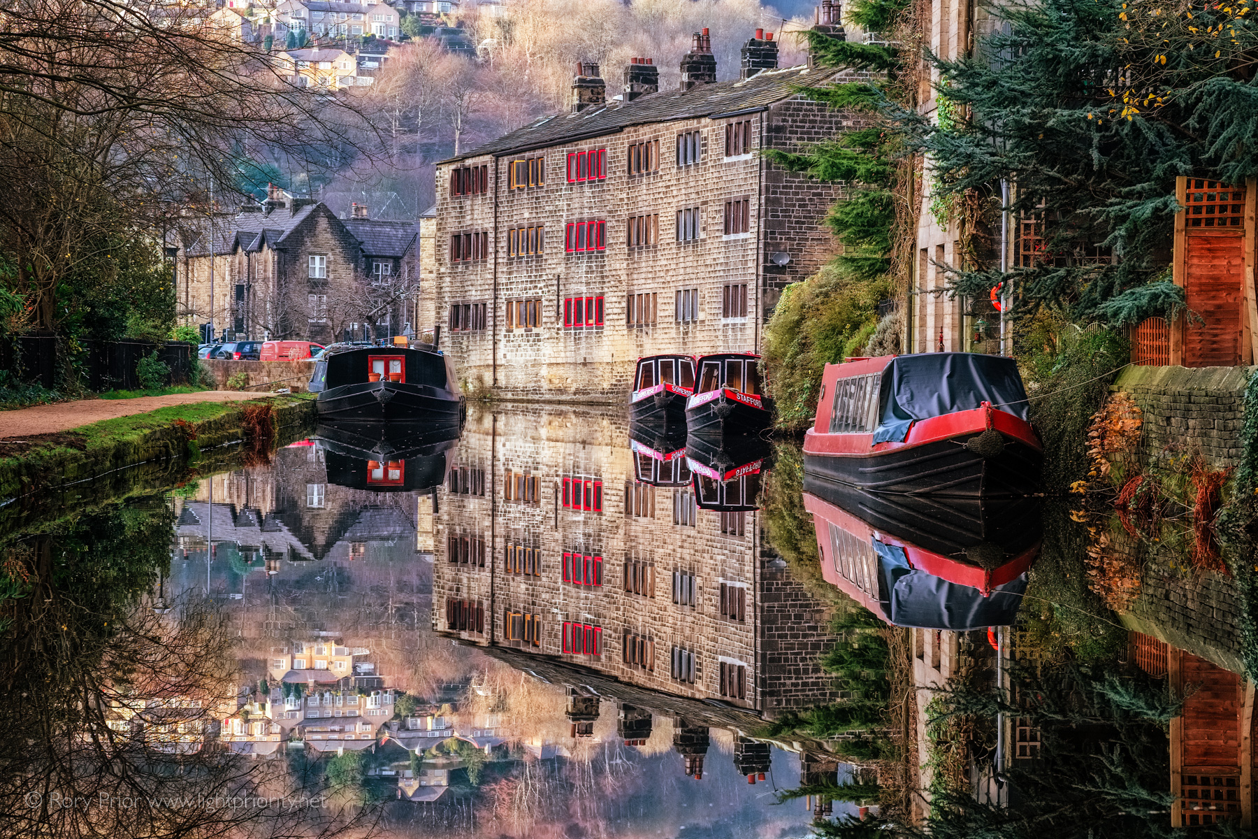 A view of the Rochdale Canal with houses and barges mirrored in the perfectly still water.
