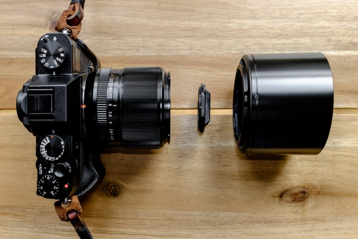 A view down on a black X-T10 with the 60mm f2 mounted with the hood and lens cap detached and placed in front of it.
